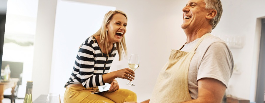 A man and woman laughing and drinking wine